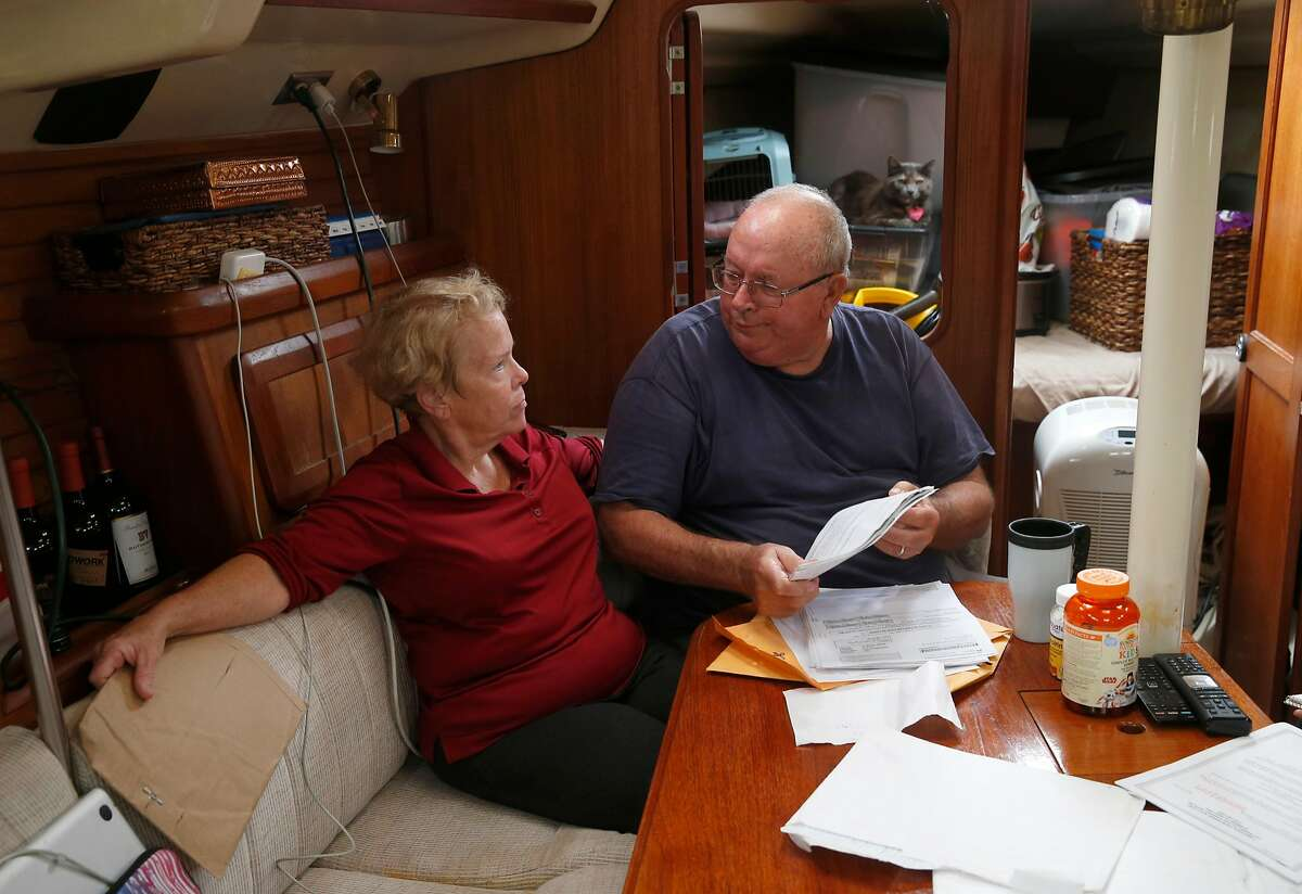 Bill and Cathy Stapp review tax returns and insurance documents aboard their sailboat Kruzin' Kitty in Alameda, Calif. on Tuesday, July 3, 2018. After being told they were eligible for the Covered California healthcare plan, the Stapp's were informed their combined income was too high to qualify for subsidized coverage and were ordered to reimburse the IRS several thousand dollars including penalty and interest.