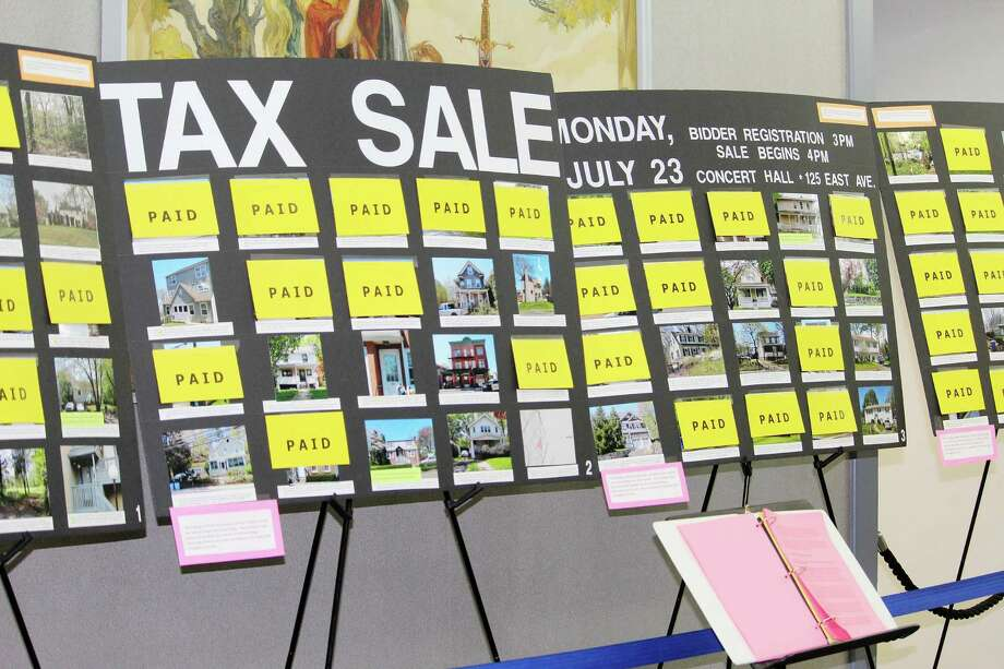 Yellow cards marked PAID cover photographs of properties removed from the 2018 Norwalk Tax Sale set for July 23 after their owners paid delinquent taxes and others unpaid fees. Photo: Robert Koch / Hearst Connecticut Media