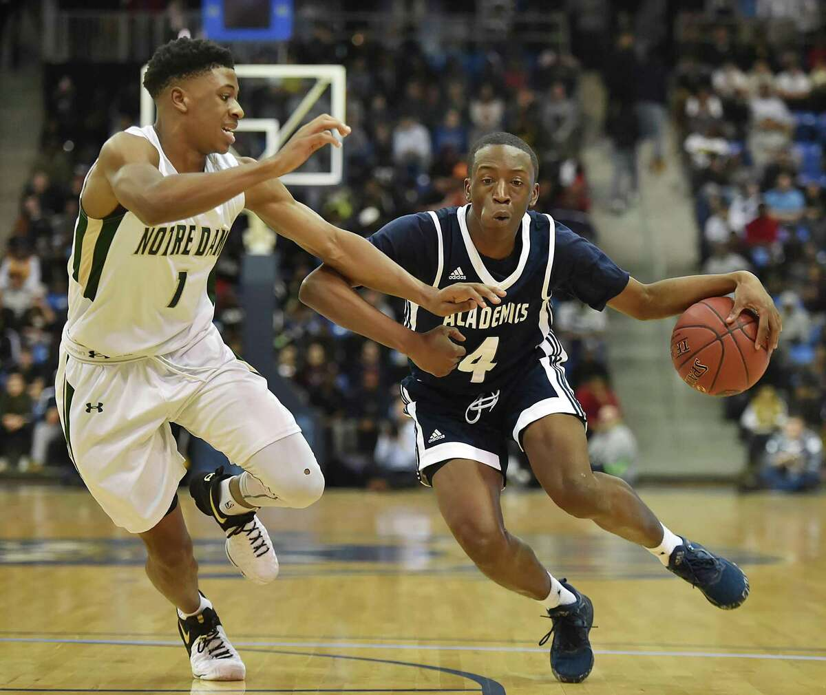 Hillhouse senior Tyler Douglas drives past Notre Dame junior Tim Dawson as the Acadmics oust the Green Knights, 70-62, for the SCC boys basketball championship, March 1, 2017, in front of a sold out crowd of 3,421- standing room only at TD Bank Sports Center at Quinnipiac University.
