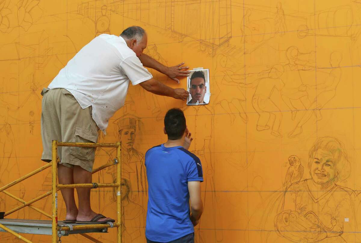 Jesse Sifuentes Jr., left, and his son Jesse Sifuentes III work on a mural titled