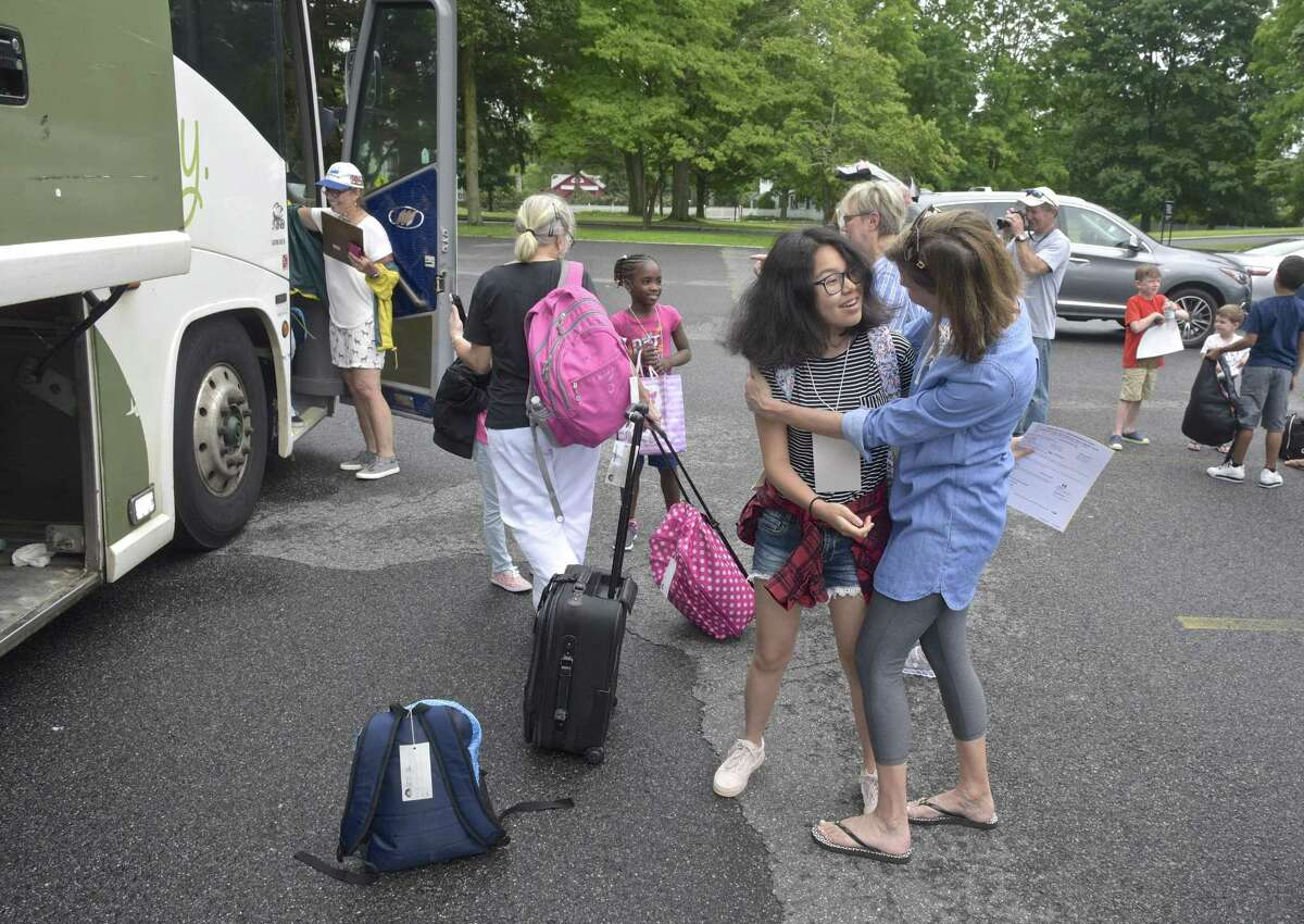 Cadence Li, 14, of New York, NY, gets a hug from Cathy Vilinskis, of Ridgefield, as she gets off a bus from New York. Li is staying with the Vilinskis's family this summer as part of the Fresh Air Fund program. Friday, July 6, 2018 in Ridgefield, Conn.