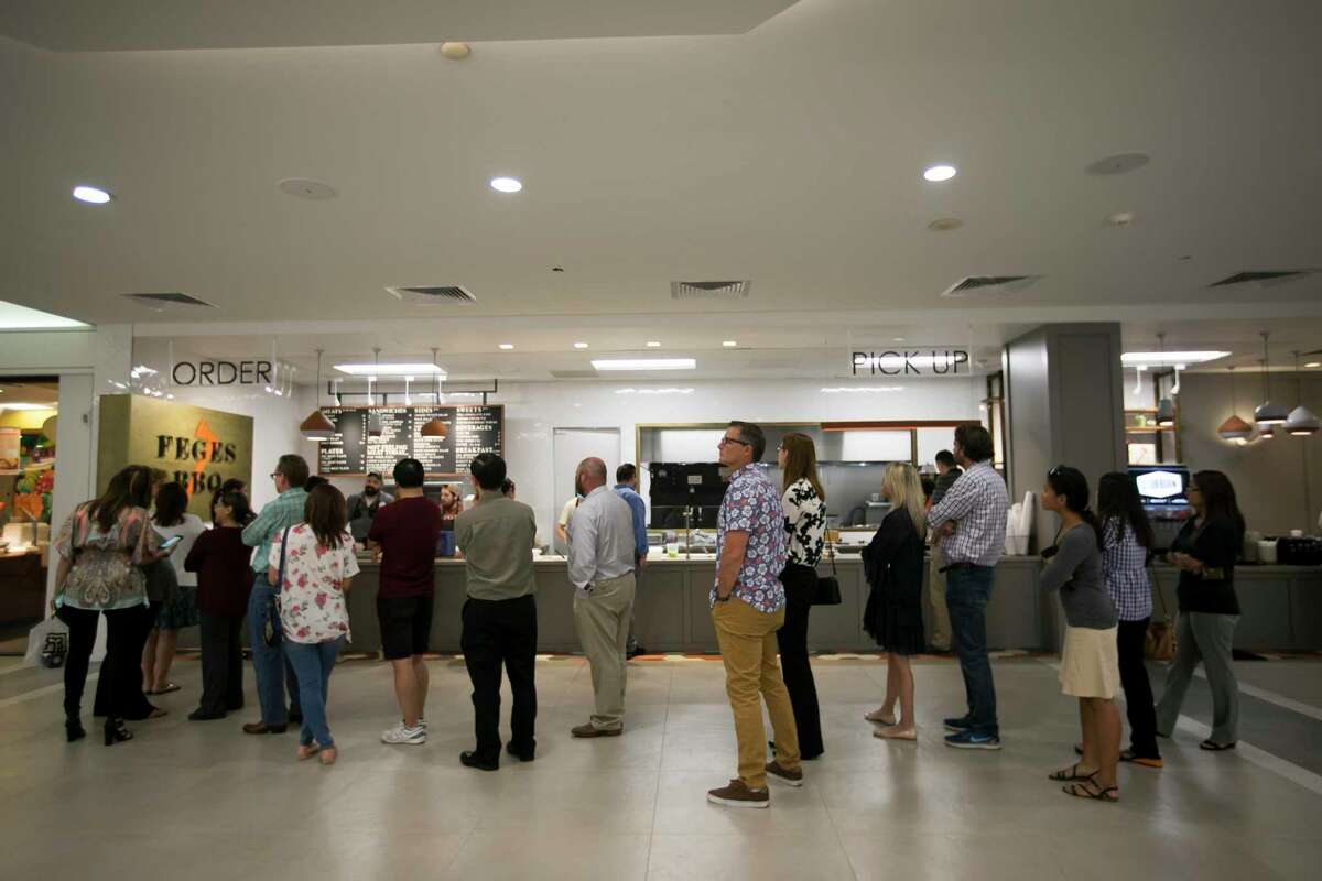 A fast-moving line forms at lunchtime at Feges BBQ in the Greenway Plaza food court.