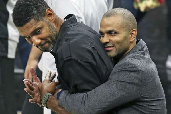 Tony Parker comes up from behind and hugs Tim Duncan who was on the court during pre game ceremonies as the Spurs play Minnesota in the season opener at the AT&T Center on October 18, 2017.