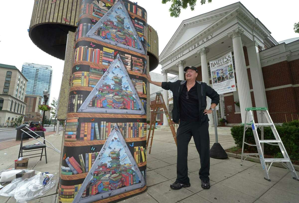 Charles Fazzino, International Master 3D Pop Artist, and his crew decorate the Kiosk structure at the Broad Street entrance of the Main branch of the Ferguson Library with butterflies as part of an art installation Friday, July 6, 2018, in Stamford, Conn.