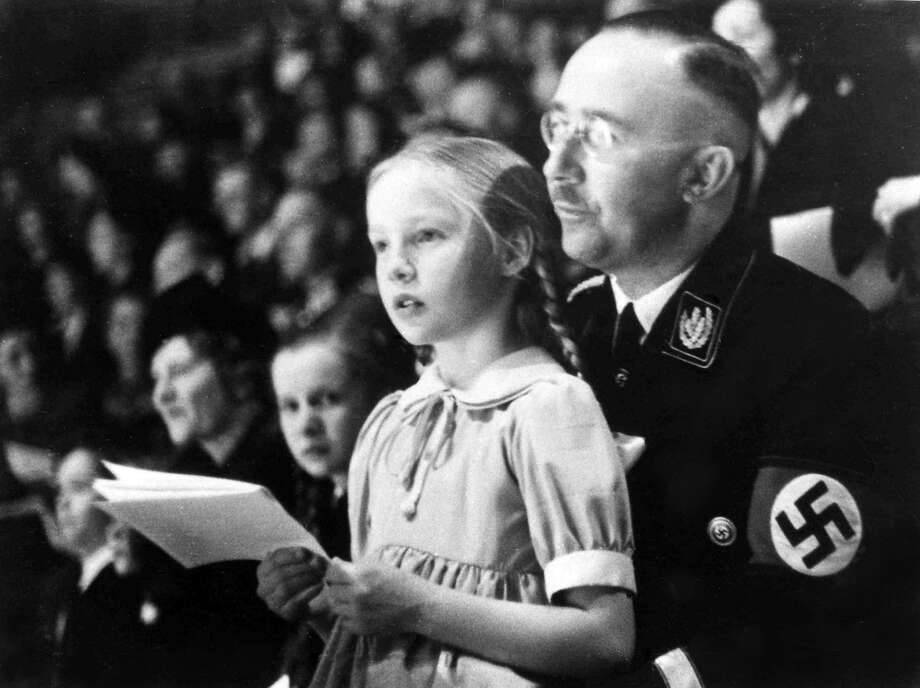 Heinrich Himmler, the No. 2 official in the Third Reich, with daughter Gudrun on his lap in 1938. Photo: Associated Press 1938