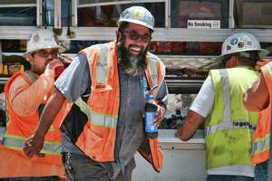 Construction workers take a rehydration break during a blistering day of heat in downtown Los Angeles on Friday, July 6, 201. Southern California baked Friday under a heat wave that forecasters correctly predicted would be one for the record books, with widespread triple-digit highs and increased fire danger. The National Weather Service says downtown Los Angeles broke the July 6, 1992 record when it hit 95 degrees. (AP Photo/Richard Vogel)