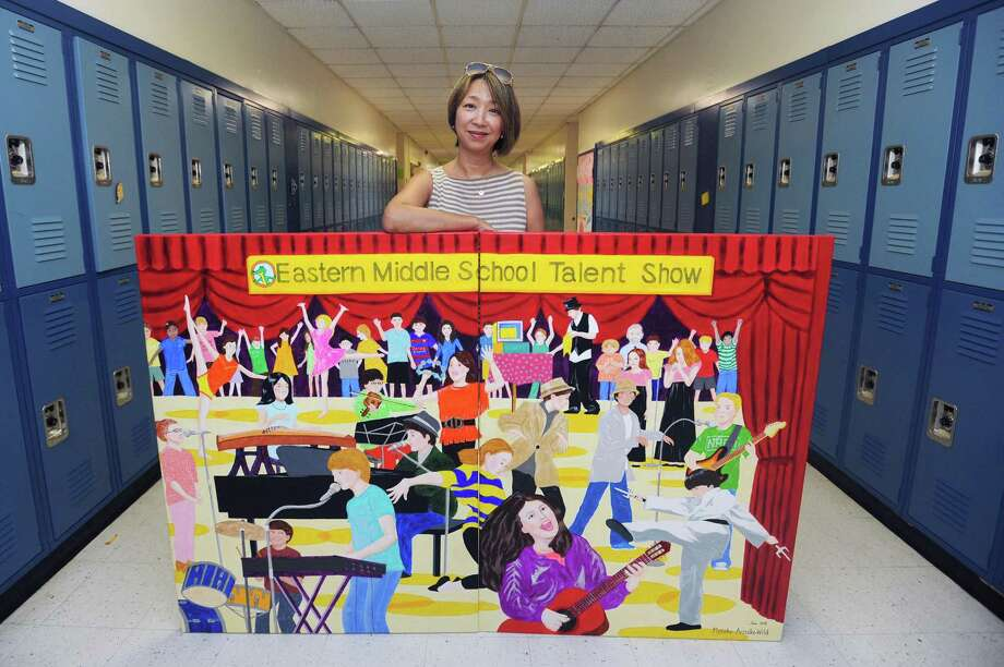 Motoko Aritake-Wilde poses next to a two-part painting she made and donated to Eastern Middle School. Photographed at the school in Greenwich, Conn. on Thursday, July 5, 2018. Photo: Michael Cummo / Hearst Connecticut Media / Stamford Advocate