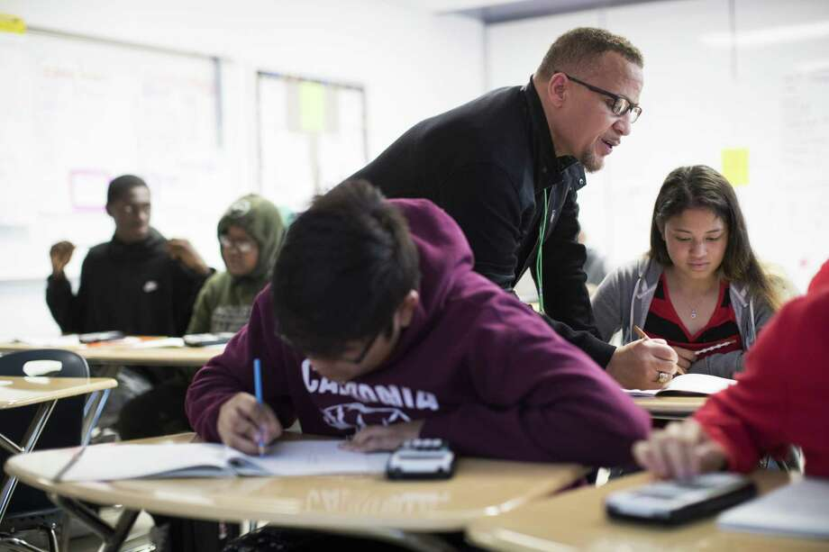 Worthing High School math teacher Michael Judge helps Hilda Martinez, 15, with questions during his Algebra I class on Thursday, April 5, 2018, in Houston.