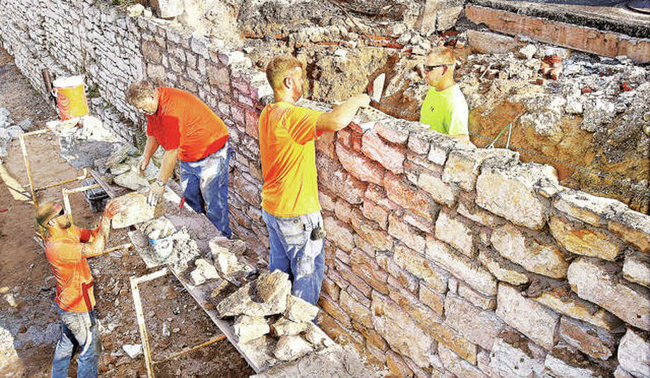 Workers from Diecker-Terry Masonry Inc. of Marissa, Illinois, rebuild the collapsed, 1800s-era limestone wall, this time secured with mortar, Friday at the corner of East Broadway and Henry Street in Alton. Recent heavy rains and sewer construction are suspected as contributing factors in the collapse. Photo:       John Badman | The Telegraph