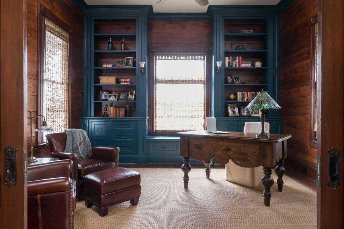 Elizabeth and Bobby Poirrier sanded off wallpaper to discover 108-year-old shiplap underneath in the study at the front of their historic home in the Heights. The floors are also original wood floors, but the built-in cabinets are new.