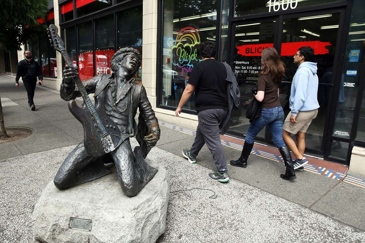 People walk past the Jimi Hendrix statue in Capitol Hill. Photographed June 14, 2017. (Genna Martin, seattlepi.com)