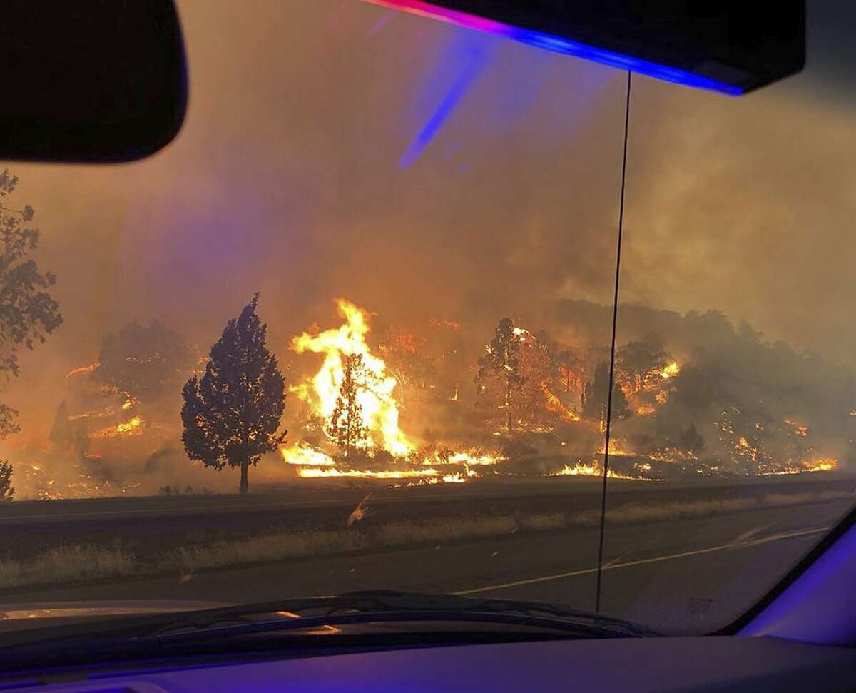 In this photo released Friday, July 6, 2018, by the California Highway Patrol, the Klamathon Fire burns in Hornbrook, Calif. A local California official says a deadly blaze burning near the Oregon border moved swiftly through the rural area that is home to many retirees. Siskiyou County Board of Supervisors chair Ray Haupt says the blaze moved so fast it quickly reached Hornbrook, a community of about 250 people about 14 miles (22 kilometers) south of the Oregon border. Authorities said one person was killed in the fire.