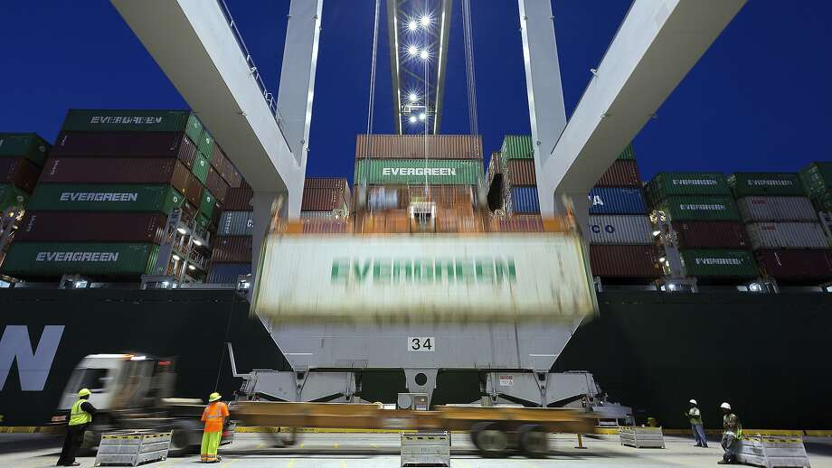 In this file photo, an Evergreen Line refrigerated container is lifted by a ship to shore crane onto the container ship Ever Linking at the Port of Savannah in Savannah, Ga. The U.S. trade deficit widened more than forecast in October to the  highest in a decade, underscoring continued fallout from the trade  dispute with China. Photo: Stephen B. Morton, Associated Press