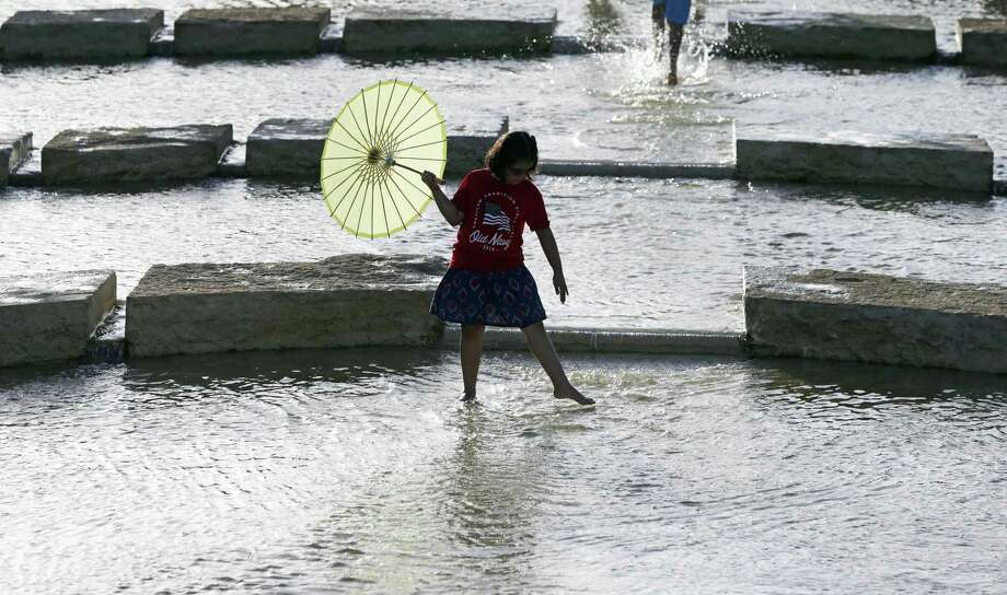 """Miriam Moyer wades in the shallow water as The San Antonio River Authority hosts """"Stroll into the Fourth"""", a pre-Fourth of July celebration at the San Pedro Creek Culture Park Tuesday. Photo: Tom Reel /San Antonio Express-News / 2017 SAN ANTONIO EXPRESS-NEWS"""