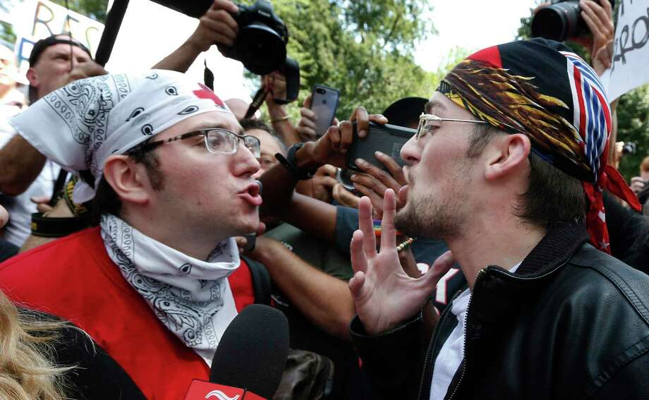 """A counterprotester confronts a supporter of President Donald Trump in Boston in 2017. A reader says we need to stop seeing one another as enemies but as """"unique creations of God."""" Photo: Michael Dwyer /Associated Press / Internal"""