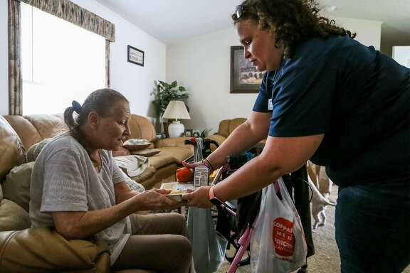 Kathy Warren, 59, receives a meal from Ariana Barber with Meals on Wheels at her home on Tuesday, June 26, 2018.  Warren was diagnosed with multiple sclerosis in 2013.MARVIN PFEIFFER/mpfeiffer@express-news.net