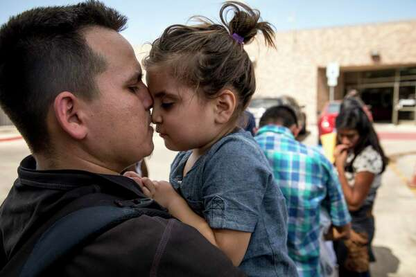 Onan, 27, carries his daughter Sofia, 3, from the bus station to the Catholic Charities of the Rio Grande Valley Respite Center after they were processed and released from detention in McAllen, Texas, Tuesday. President Trump's zero-tolerance policy is nonetheless resulting in the unnecessary detention of immigrant families.