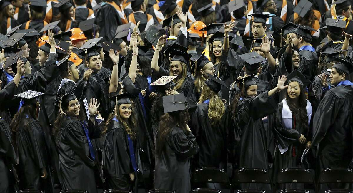 """University of Texas at San Antonio graduates wave to family and friends during the commencement ceremonies in December 2013 at the Alamodome. The Bureau of Labor Statistics says the value of a university degree is """"softening."""""""