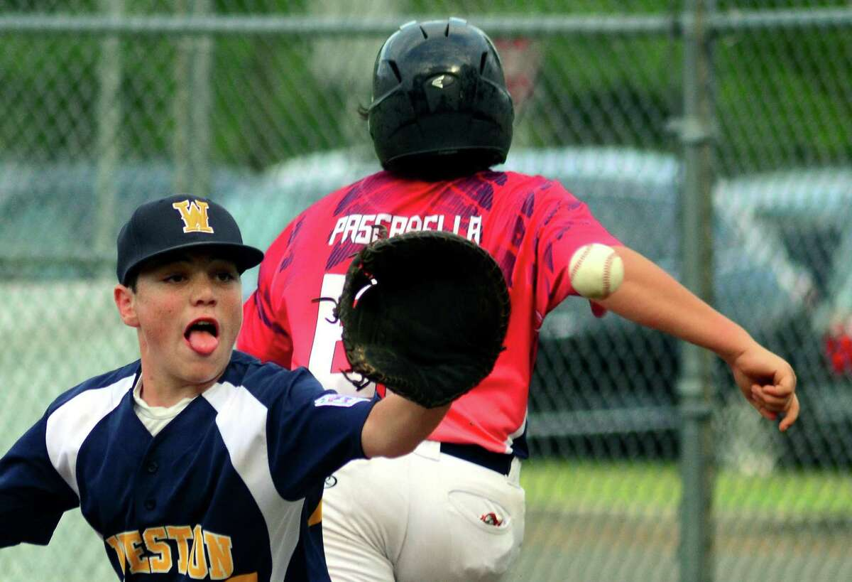 Weston first baseman Ben Landesman receives the ball as Stamford's Jack Pascarella reaches the base safely during District 1 little league baseball action at Scalzi Park in Stamford, Conn., on Friday July 6, 2018.