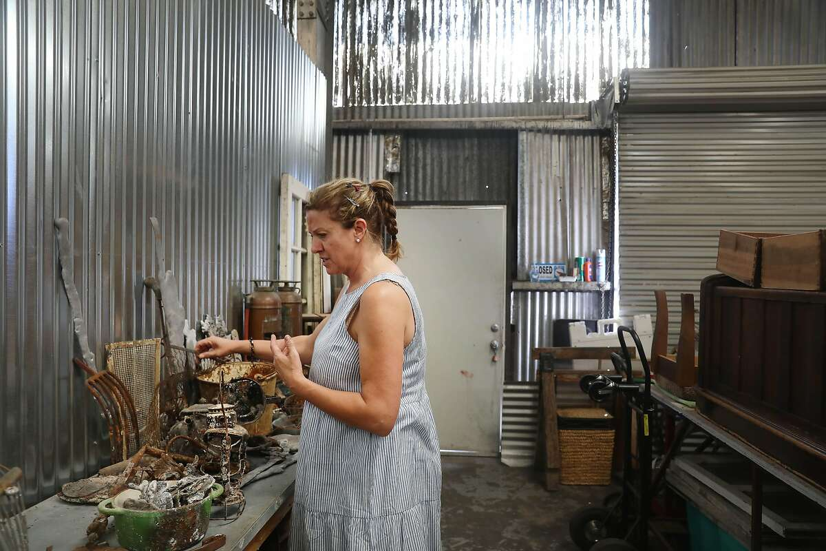 Artist Helena Donzelli looks through different pieces of debris she has collected left from the North Bay fires in the studio she shares with Peter Alan and Karen Ingalls on Thursday, July 5, 2018 in Sonoma, Calif. Donzelli lost her studio home in the North Bay fires.