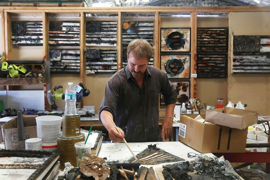 Peter Alan works on a piece of art which uses debris left from his studio which burned in the North Bay fires last year. Photo: Lea Suzuki / The Chronicle