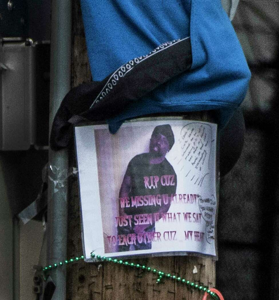 A photo copy of an image of a man is tacked to the utility pole at the makeshift memorial for the murder victim from 297 Orange Street at the corner of Lark and Orange Streets Friday July 6, 2018 in Albany, N.Y. (Skip Dickstein/Times Union)