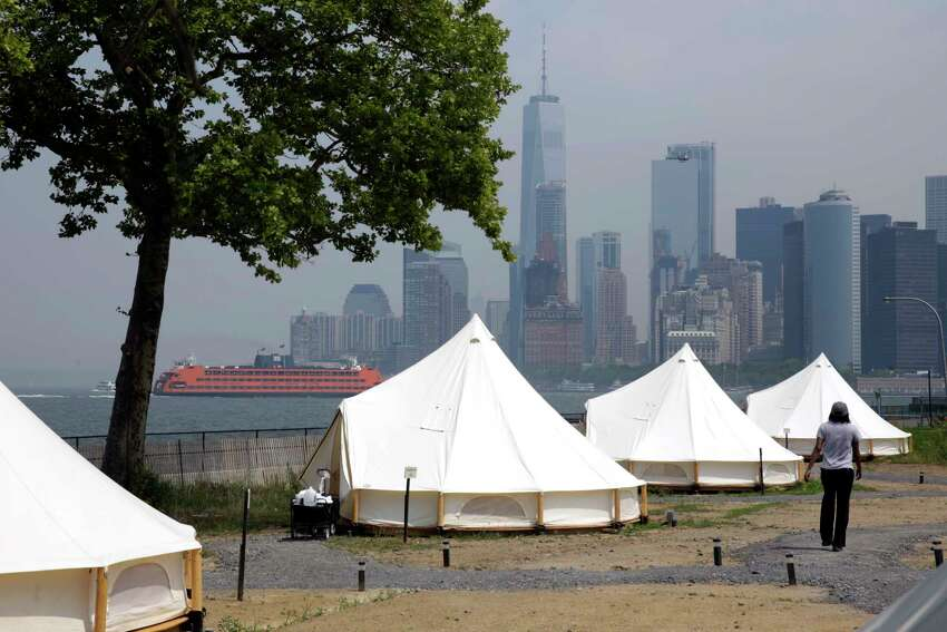 In this July 3, 2018 photo, some of Collective Retreats' Journey Tents sit on Governor's Island Island, in New York Harbor, below Manhattan's southern end, seen in background. Guests staying at the Collective Retreats campsite on Governor's Island will have views of the Statute of Liberty and stay in furnished, luxury tents that cost as much as a Manhattan hotel room. (AP Photo/Richard Drew)