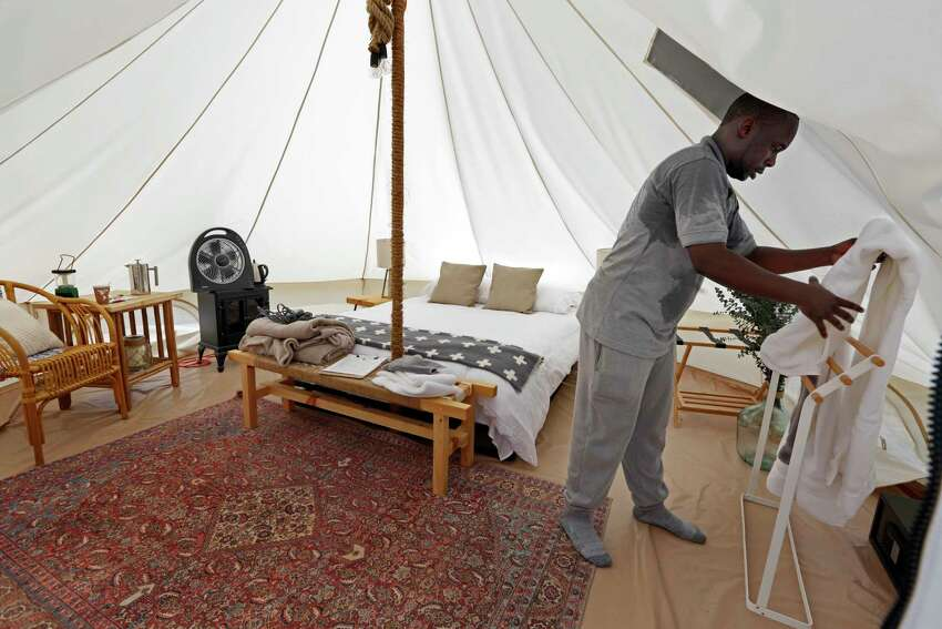 In this July 3, 2018 photo, housekeeping worker Deijon Wright makes up one of Collective Retreats' Journey Tents on Governor's Island, in New York harbor, Tuesday, July 3, 2018. Guests staying at the Collective Retreats campsite on Governor's Island will have views of the Statute of Liberty and stay in furnished, luxury tents that cost as much as a Manhattan hotel room. (AP Photo/Richard Drew)