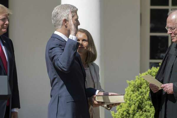 Supreme Court Justice Anthony Kennedy, right, administers an oath of office to Justice Neil Gorsuch, at the Rose Garden of the White House on April 10, 2017. Kennedy, who has long been the decisive vote in many cases, announced his intent to retire on June 27, 2018, setting the stage for a furious fight over the future direction of the Supreme Court.