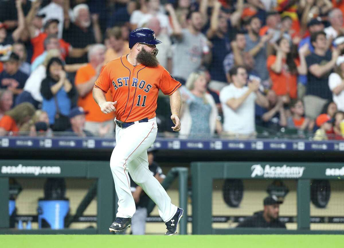 Houston Astros designated hitter Evan Gattis (11) watches Marwin Gonzalez (9) run behind him as they score off of a double by Tim Federowicz (19) against the Chicago White Sox at the Minute Maid Park on Friday, July 6, 2018 in Houston.