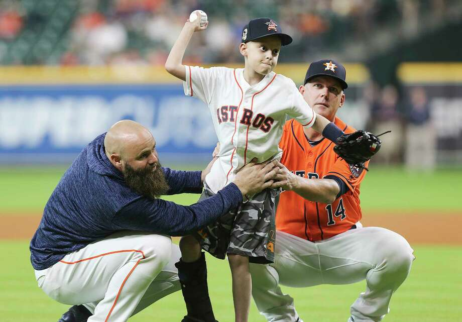 Cameron Gooch, 10, gets a little help from Astros manager AJ Hinch (14) and  designated hitter Evan Gattis (11) for the ceremonial first pitch before Friday's game against the White Sox at Minute Maid Park. Photo: Elizabeth Conley, Houston Chronicle / ©2018 Houston Chronicle