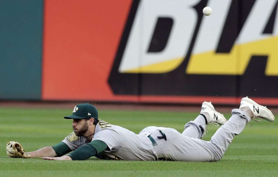 Oakland's Dustin Fowler dives but can't make a grab on a ball hit by Cleveland's Michael Brantley in the third inning. Photo: Tony Dejak / Associated Press