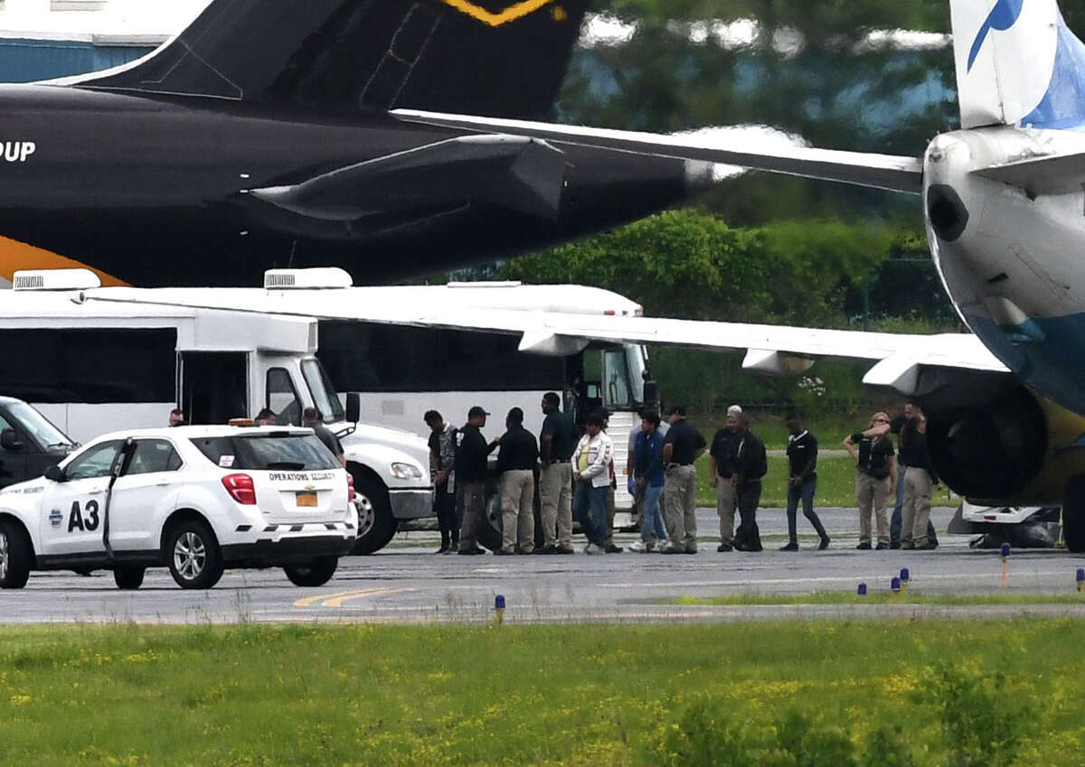 Immigrant men are escorted off a U.S. Immigration and Customs Enforcement jet from Arizona at Albany International Airport during their transport to Albany County Jail on Thursday afternoon, June 28, 2018, in Colonie, N.Y. The jail has taken in 235 immigrant men who are being detained on immigration charges. (Will Waldron/Times Union)