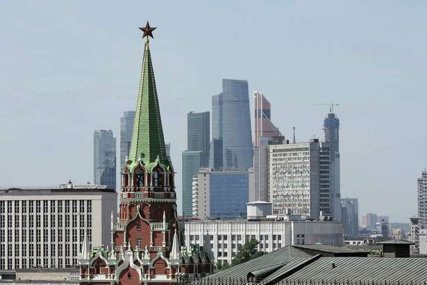 A tower of the Kremlin stands in front of skyscrapers in Moscow on May 27, 2018.