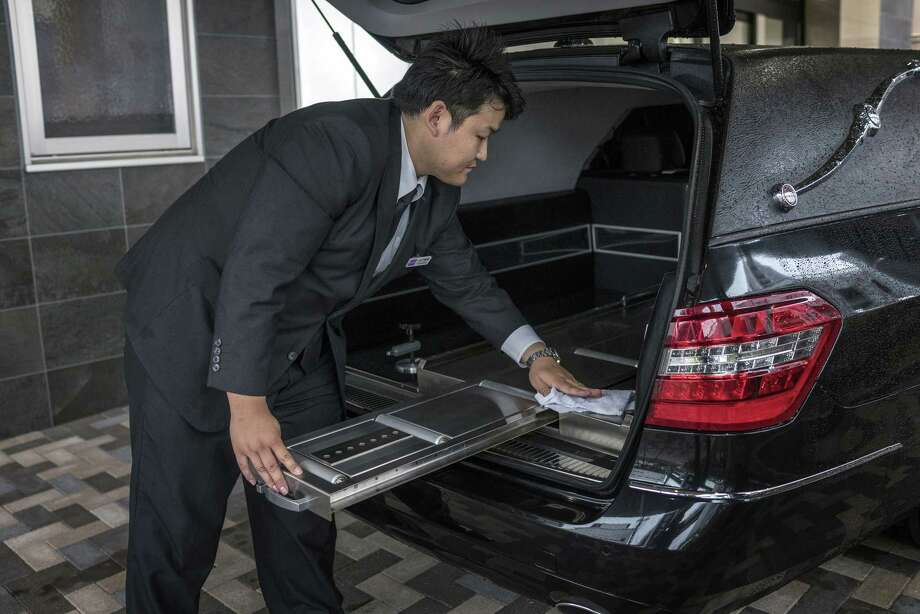 A Tear Corp. driver cleans the back of a Mercedes-Benz hearse outside the company's headquarters in Nagoya, Japan, on June 20, 2018. Photo: Bloomberg Photo By James Whitlow Delano. / © 2018 Bloomberg Finance LP