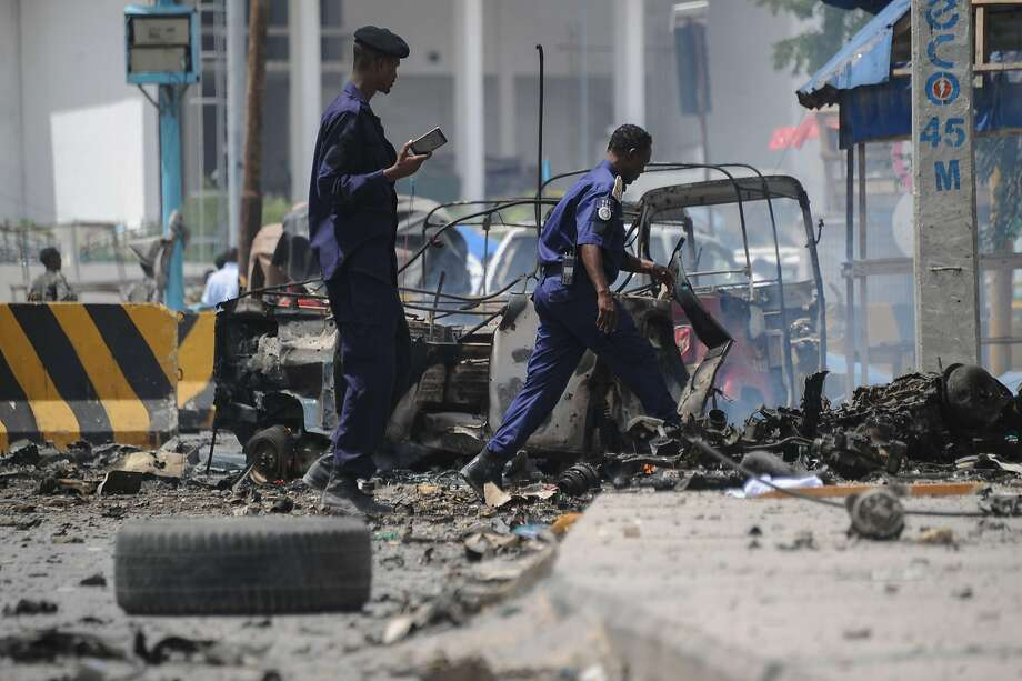 Security forces examine the wreckage of burned vehicles at the site of an attack by militants in the capital of Mogadishu. Photo: Mohamed Abdiwahab / AFP / Getty Images