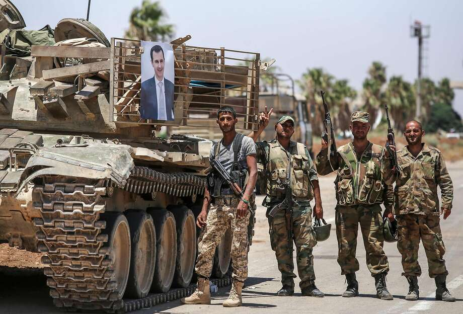 Syrian soldiers flash the victory sign next to a picture of President Bashar Assad hanging on a tank at the Naseeb border crossing with Jordan in the southern province of Daraa. Photo: Youssef Karwashan / AFP / Getty Images