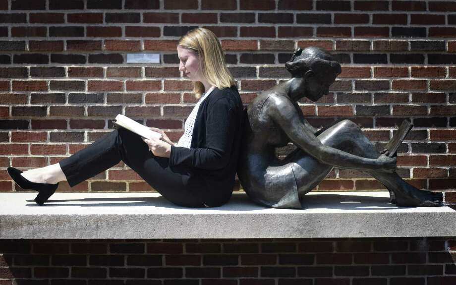 "New Cos Cob Library Branch Manager Laura Matthews reads a Shel Silverstein book against Margaret Koehler Nicholson's sculpture ""The Bequest of Wings"" outside the Cos Cob Library in the Cos Cob section of Greenwich, Conn. Wednesday, July 5, 2018. Matthews plans to take a forward-thinking approach to her duties as she replaces Wendy Silver, who retired after 39 years as Branch Manager earlier this year. Photo: Tyler Sizemore / Hearst Connecticut Media / Greenwich Time"