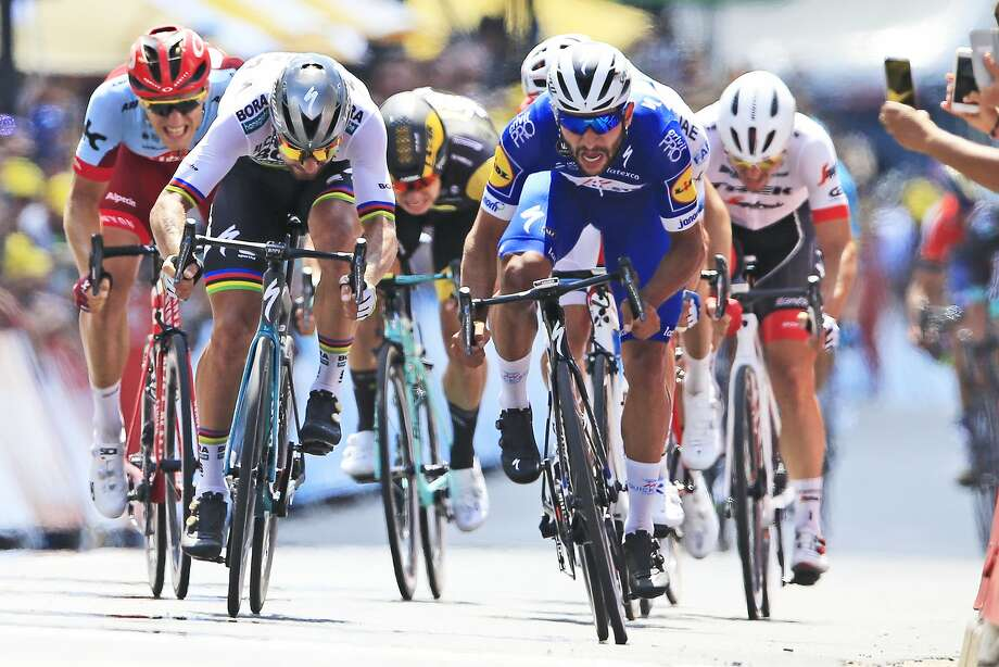 Colombia's Fernando Gaviria (in blue) crosses the finish line ahead of Peter Sagan of Slovakia (left) to win the first stage of the Tour de France on Saturday. Photo: Peter Dejong / Associated Press