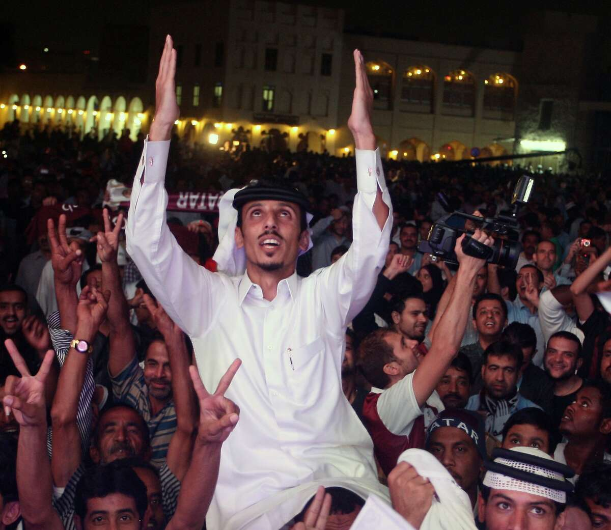Qataris react in the streets, after the announcement that Qatar will host the soccer World Cup in 2022, in Doha, Thursday, Dec. 2, 2010. (AP Photo/Osama Faisal)