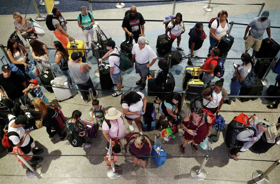 FILE - In this June 29, 2018, file photo, people wait in line to check in at McCarran International Airport in Las Vegas. he summer air travel season is shaping up to be the busiest ever, which could mean lengthy lines at U.S. airport security checkpoints. But you can use the faster lanes if you belong to an expedited screening program, which could essentially be free to join with the right credit card. The primary federal programs for air travel, TSA Precheck and Global Entry , cost $85 or $100 per traveler, respectively, and enrollment lasts five years for both. (AP Photo/John Locher, File) Photo: John Locher / Copyright 2018 The Associated Press. All rights reserved.