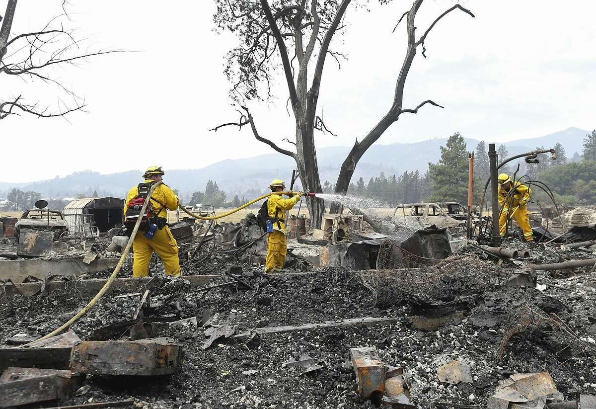 Lake Forest volunteer firefighters from left, Kyle Potter, Dylan Beck and Jerod Ellis work on putting out hot spots in an area burned down by the Klamathon Fire Friday, July 6, 2018, in Hornbrook, Calif. California officials say they are temporarily closing a hatchery and two other public areas because of their proximity to a deadly blaze near the Oregon state line. The California Department of Fish and Wildlife says the Iron Gate Fish Hatchery along the Klamath River, the Klamathon Road fishing access below the hatchery and the Horseshoe Ranch Wildlife Area have been closed as a precaution. (Greg Barnette/The Record Searchlight/USA TODAY Network via AP)