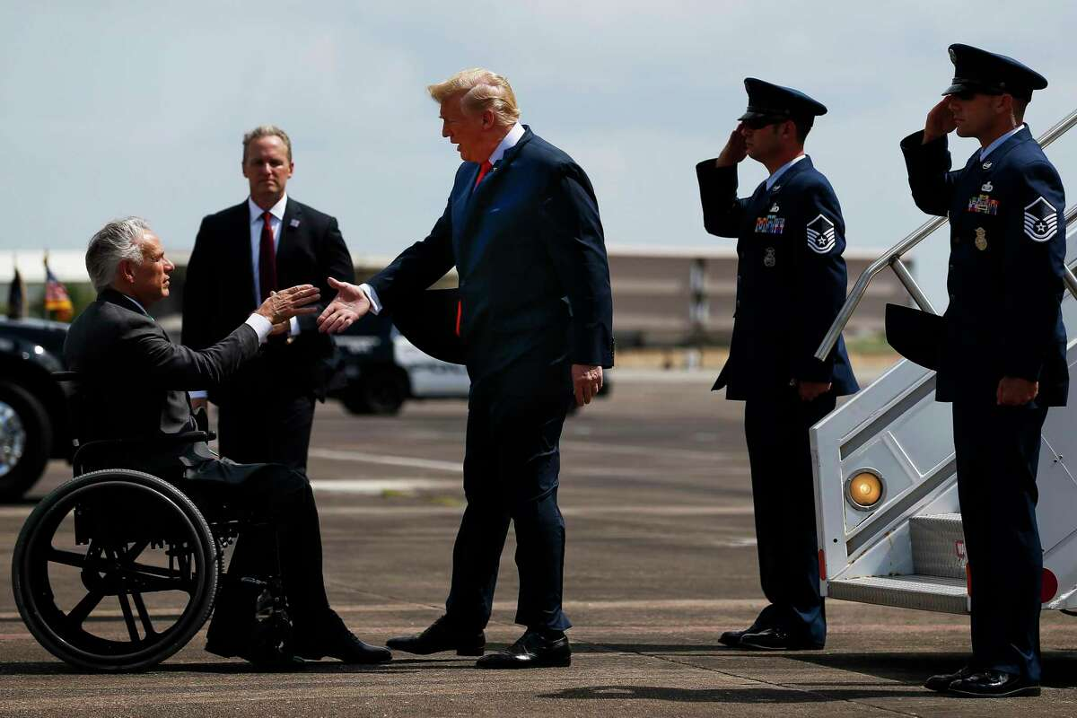 """President Donald Trump shakes hands with Governor Greg Abbott after landing at Ellington Field Joint Reserve Base on May 31, 2018 in Houston. Abbott said Friday the state will reject the re-settlement of new refugees, becoming the first state known to do so under a recent Trump administration order. He saidTexas, which typically takes in thousands of refugees each year, has done """"more than its share."""" Governors in 42 other states have said they will consent to allowing in more refugees."""