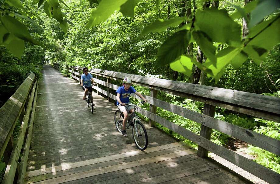 Nancy Fisher, of Trumbull, in back and her daughter Victoria, 12, cross a bridge along the Pequonnock River bike trail near Old Mine Park in Trumbull, Conn.  Photo: Christian Abraham / Hearst Connecticut Media / Connecticut Post