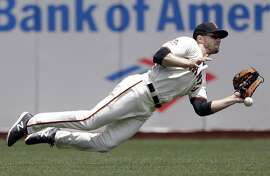 San Francisco Giants left fielder Austin Slater dives for but cannot catch a line drive from St. Louis Cardinals' Kolten Wong during the third inning of a baseball game Saturday, July 7, 2018, in San Francisco. (AP Photo/Marcio Jose Sanchez)