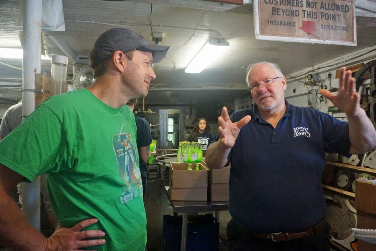 U.S. Sen. Chris Murphy (left) spoke to Avery's Beverages general manager Rob Metz (right) in New Britain, Conn. on Saturday July 7, 2018 during his third annual walk across the state.