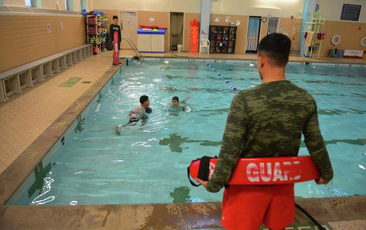 FILE PHOTO - Lifeguard Connor Martinez, watches as Bryan Mota, 8, and Josiah Cruz, 9, play in the pool at the Cardinal Sheehan Center in Bridgeport, Conn., on Thursday Jan. 12, 2017.