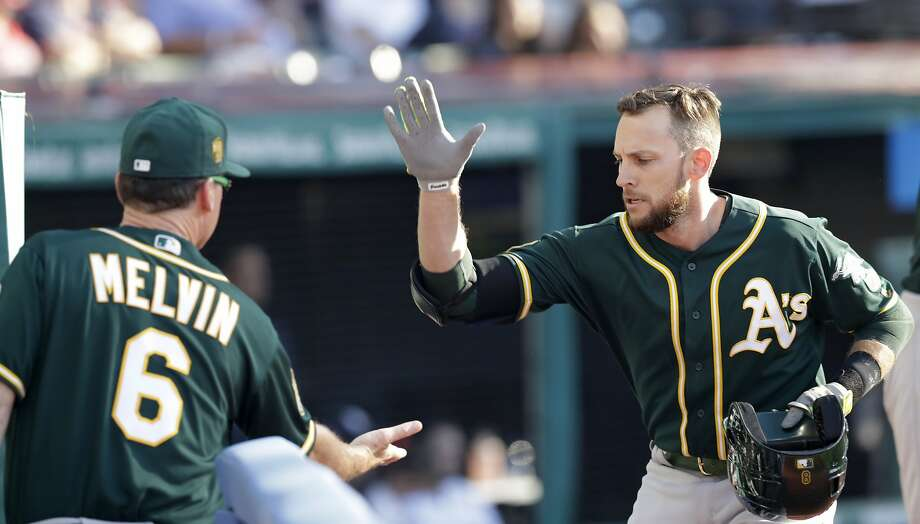 Oakland Athletics' Jed Lowrie, right, is congratulated by manager Bob Melvin after Lowrie hit a two-run home run in the eighth inning of a baseball game against the Cleveland Indians, Saturday, July 7, 2018, in Cleveland. Mark Canha scored on the play. Photo: Tony Dejak / Associated Press