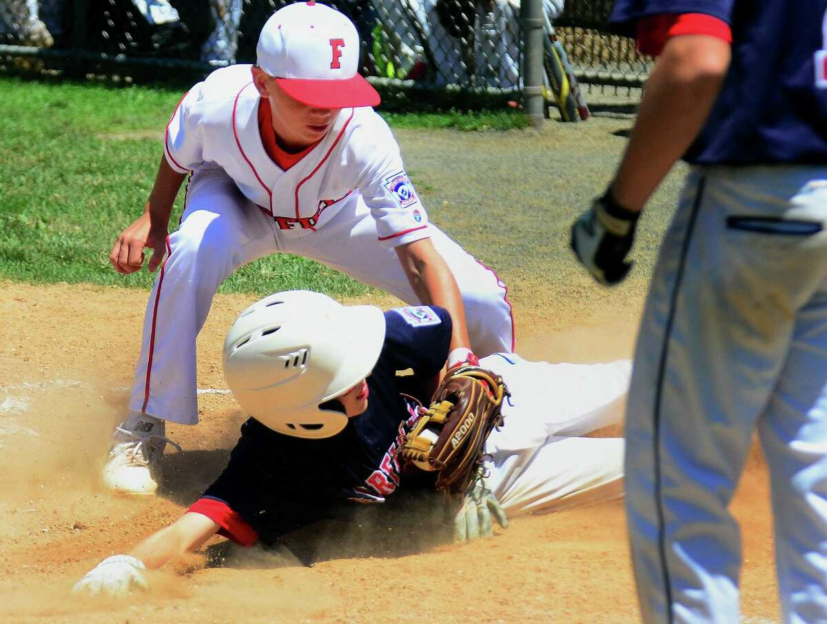 Fairfield National's Ryan Oshimski slides safely into home plate as Fairfield American pitcher Jon Morris tries to make the tag during National's 10-3 victory on Saturday at Unity Park in Trumbull