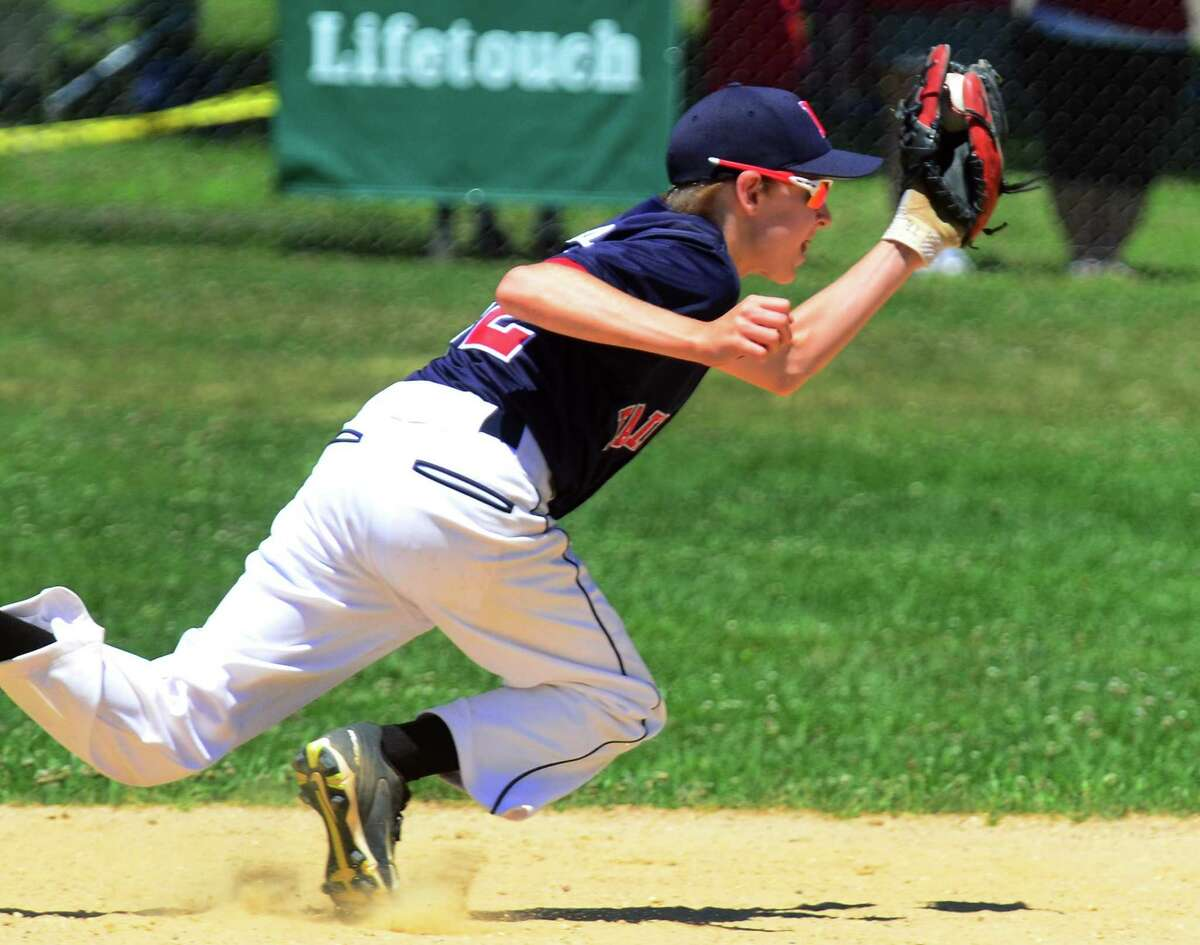 Fairfield National's Ryan Oshimski stops a Fairfield American hit during District 2 little league baseball action at Unity Park in Trumbull, Conn., on Saturday July 7, 2018.